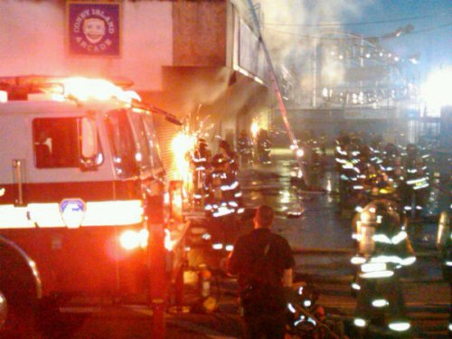 Firefighters sawing into Coney Island Arcade thru the shutters to access fire.  Photo © Adam Richman via twitpic